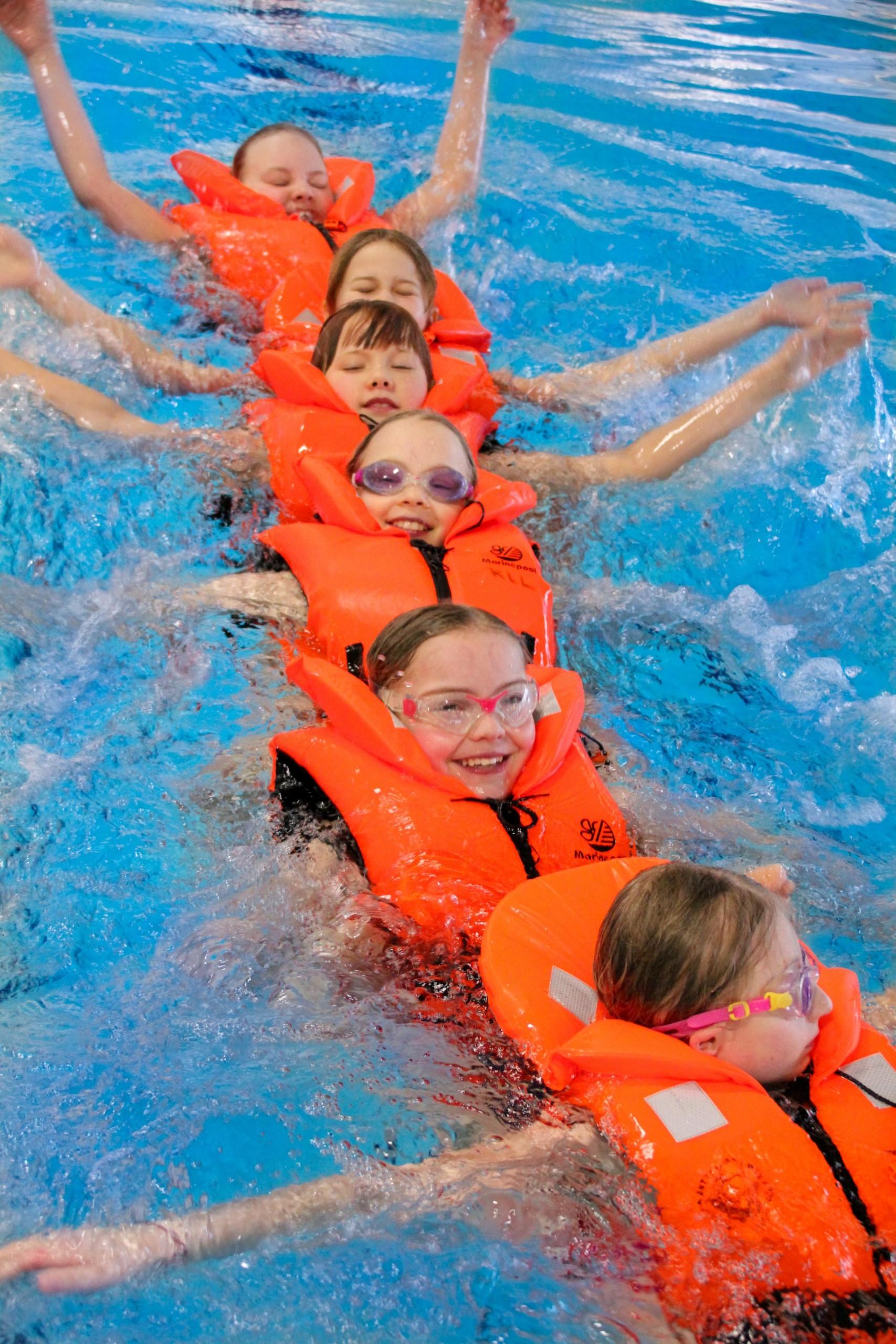 Lapset uivat selällään letkassa pelastusliivit päällä
