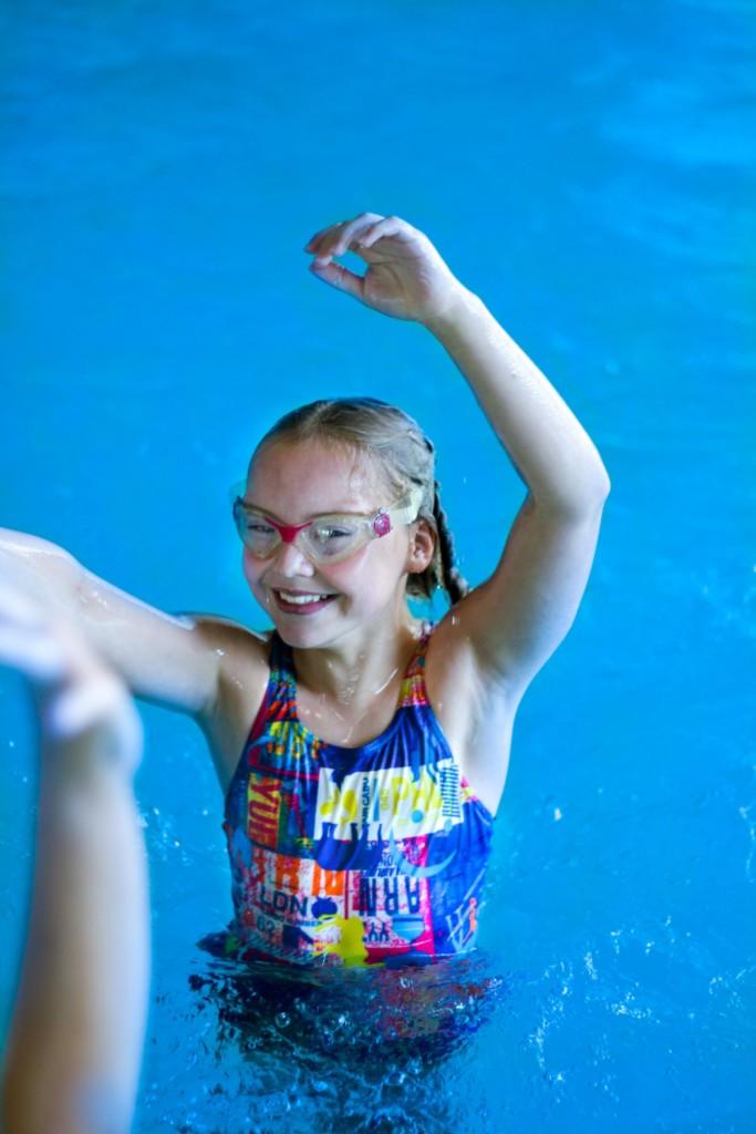 Tyttö seisoo vedessä kädet ilmassa.
