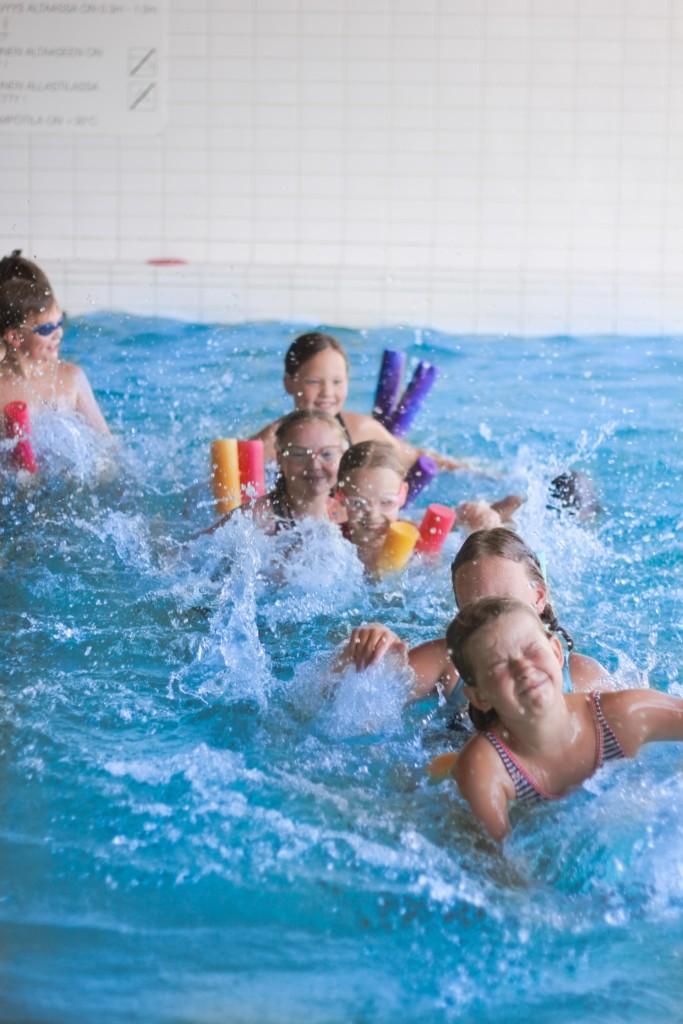 Lapset leikkivät vedessä hippaa.