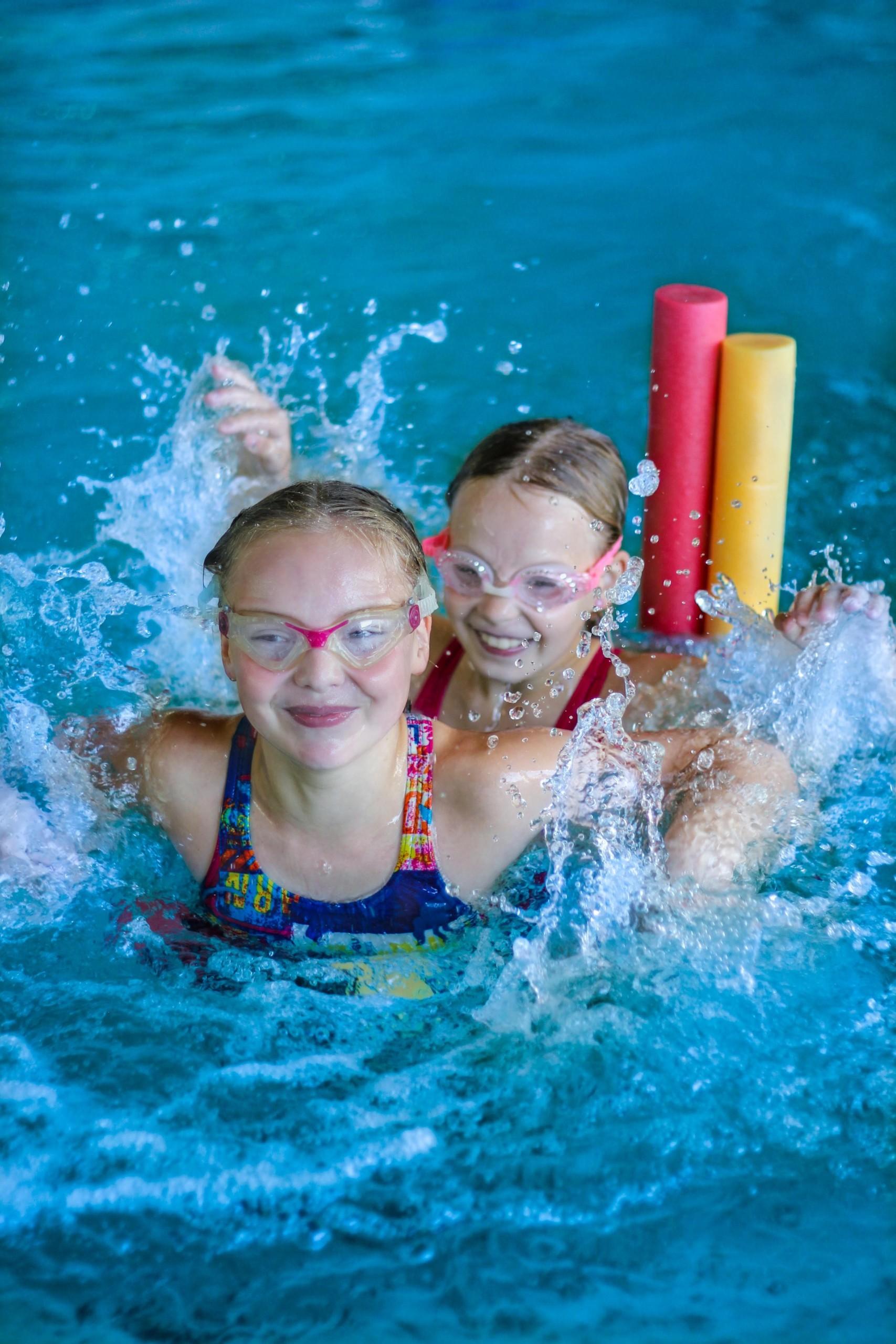 Tytöt pärskyttävät innoissaan vettä lötköpötköjen päällä