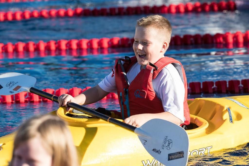 Poika on iloisena melomassa pelastusliivit päällä.