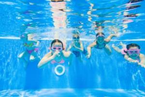 Lapset sukeltavat veden alla uima-altaassa kameraa kohti.